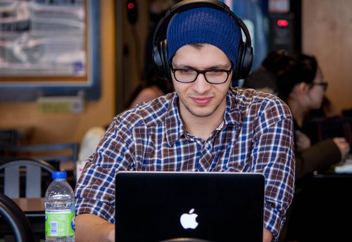 guy in plaid shirt and beanie, wearing headphones, working on a macbook